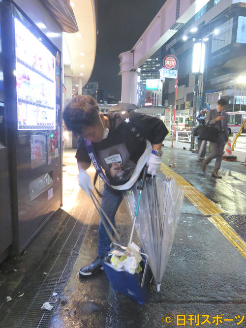 雨の降る中、渋谷ハチ公前広場でゴミを拾うカラテカ入江慎也
