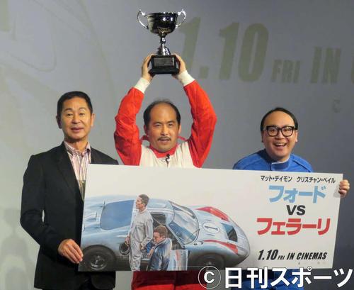 伝説のレーサー、ドリキンこと土屋圭一氏(左)にレーシングゲームで勝ってトロフィーを掲げるトレンディエンジェル斎藤司(中央)とたかし