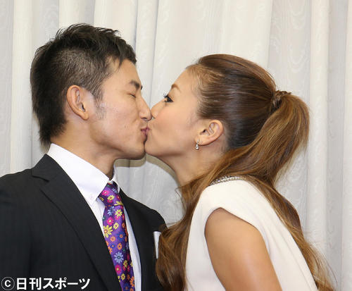 結婚会見でキスをする才賀紀左衛門(左)とあびる優(2014年9月19日撮影)