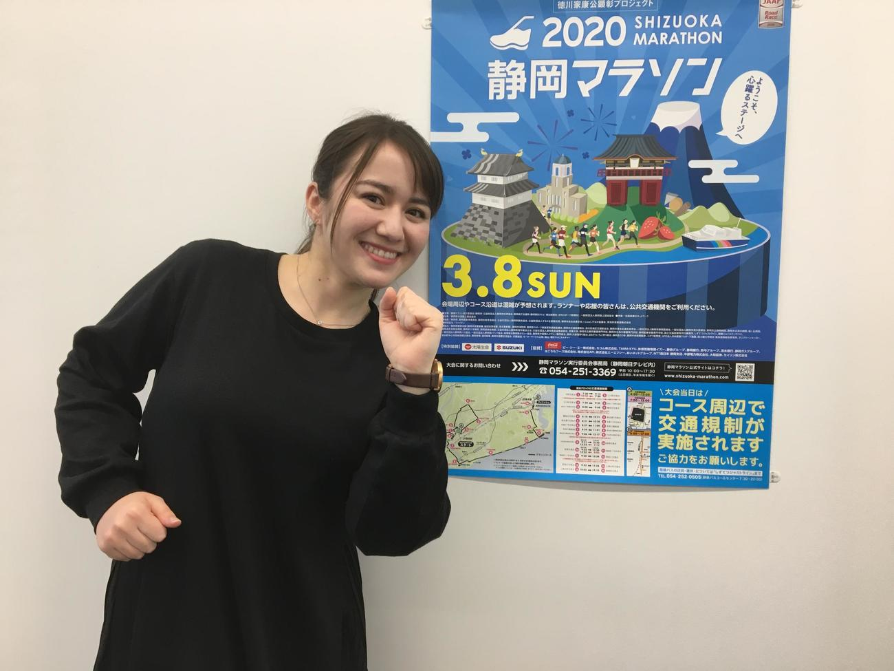 静岡朝日テレビのスミス春子アナウンサーは、静岡マラソンのPRポスターの前でランニングポーズを披露