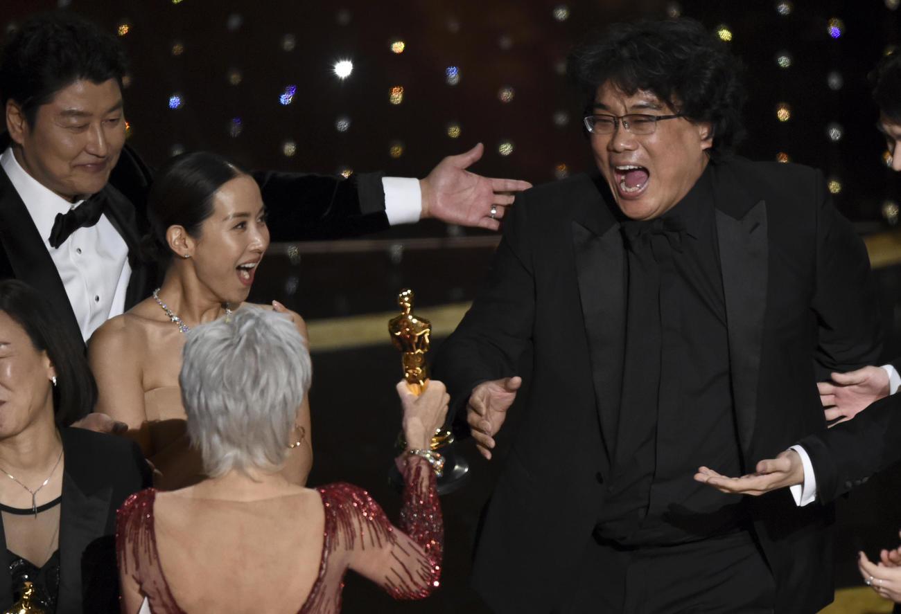 作品賞に輝き喜ぶ「パラサイト 半地下の家族」のポン・ジュノ監督(右=AP)