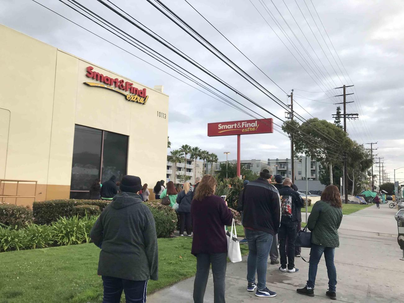 入店制限が設けられたスーパーマーケットに並ぶ市民の列は歩道にまで続いている