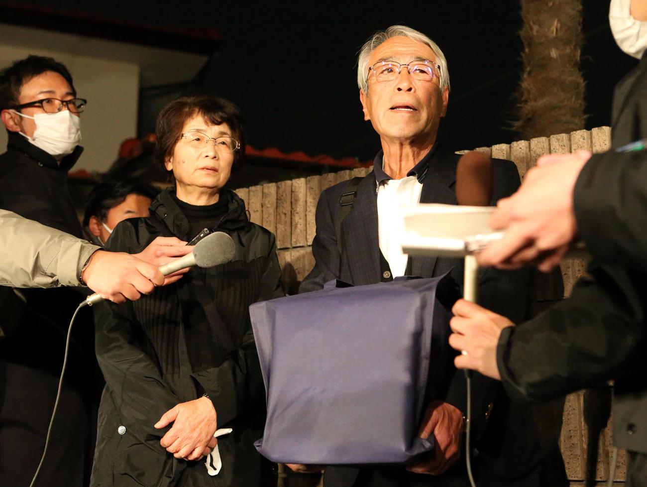 亡くなった志村けんさんの遺骨を抱き、実家の前で報道陣の質問に答える兄知之さん(右)。左は妻のサヨ子さん(撮影・狩俣裕三)