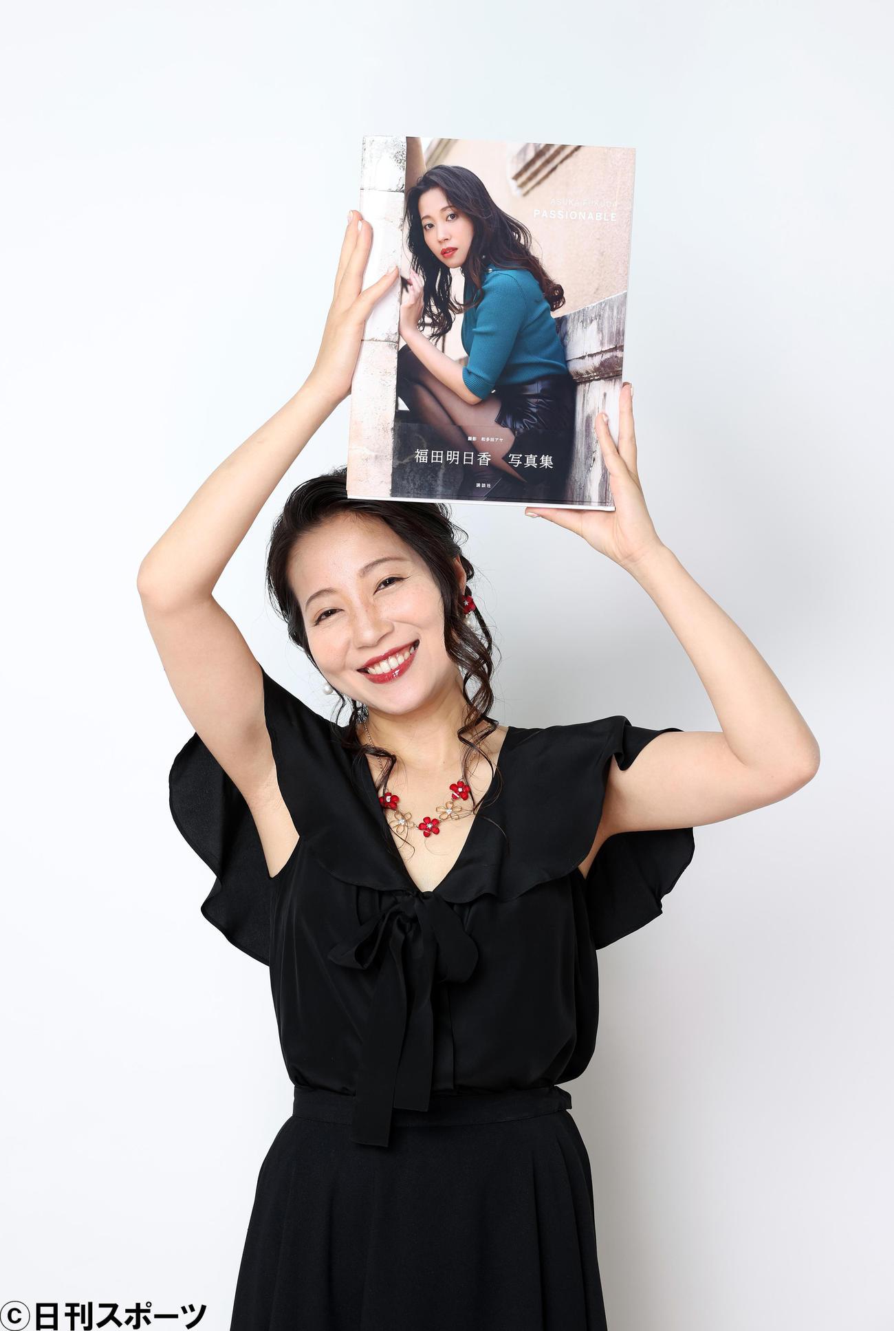 うれしそうに写真集「PASSIONABLE」を手にする福田明日香(撮影・大野祥一)