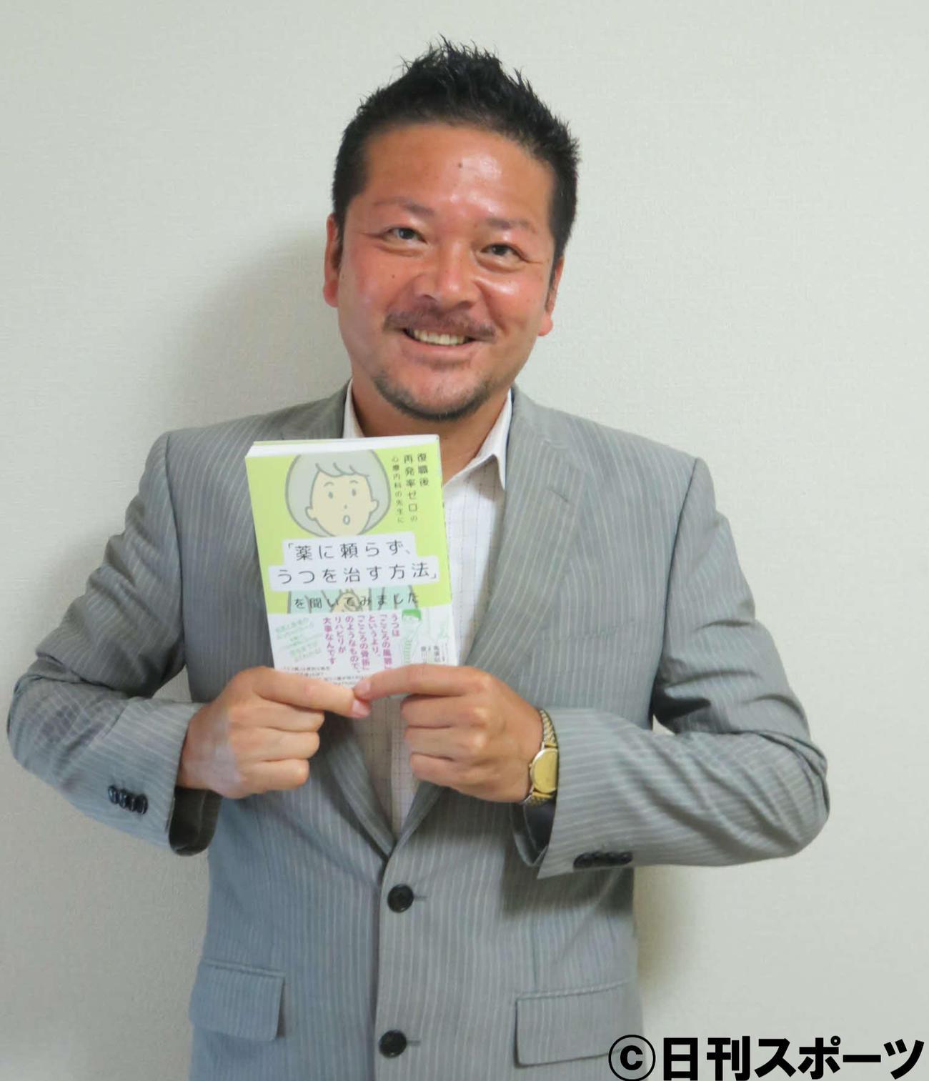 著書を手にする作家夏川立也氏