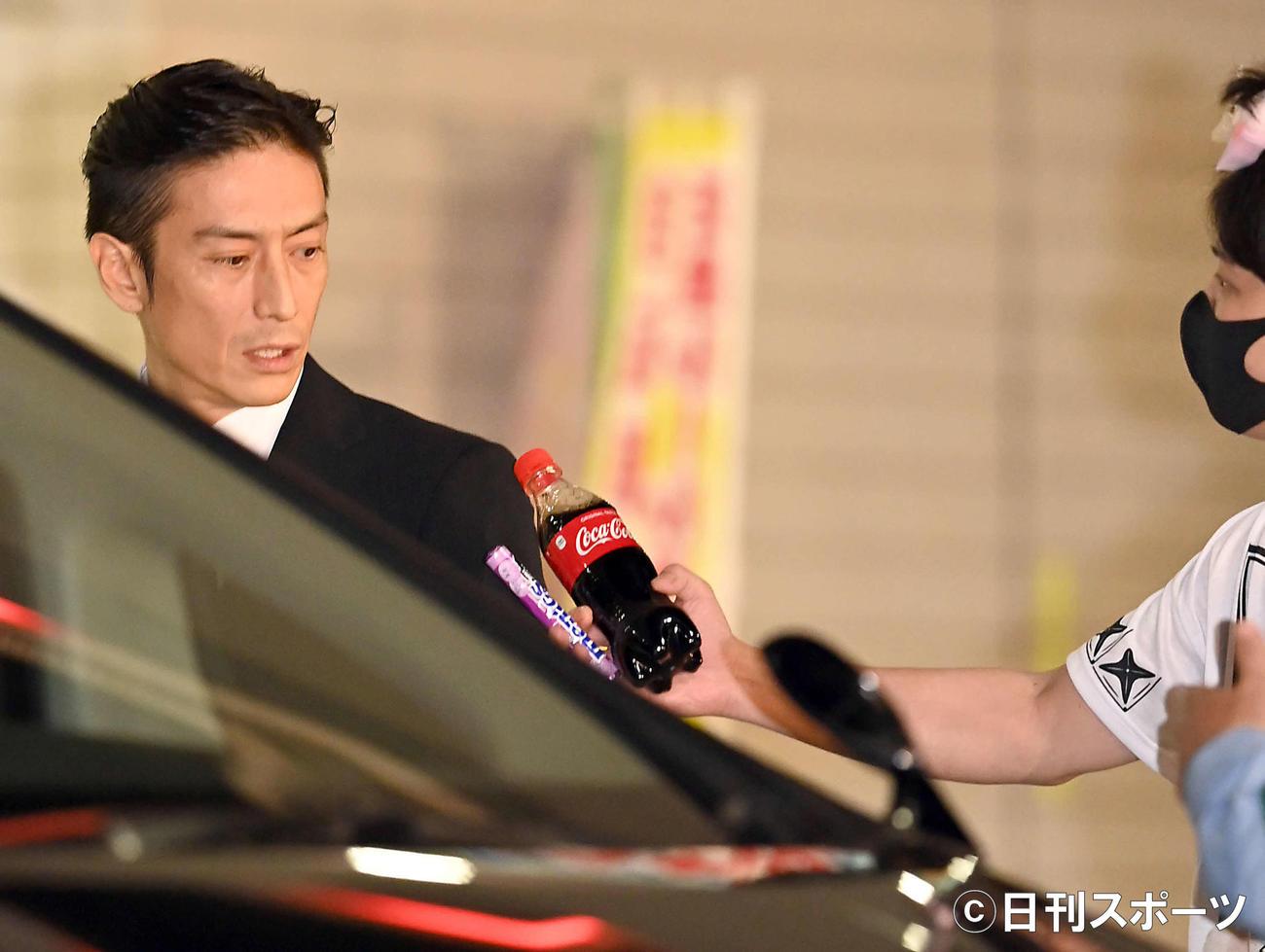保釈され車に乗り込む伊勢谷友介被告は、乱入者に飲料水とお菓子を差し出される(撮影・たえ見朱実)