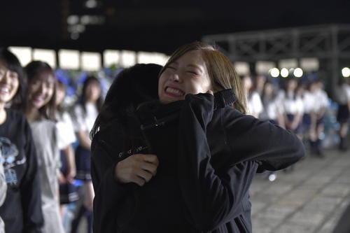メンバーと抱き合って笑顔を見せる白石麻衣
