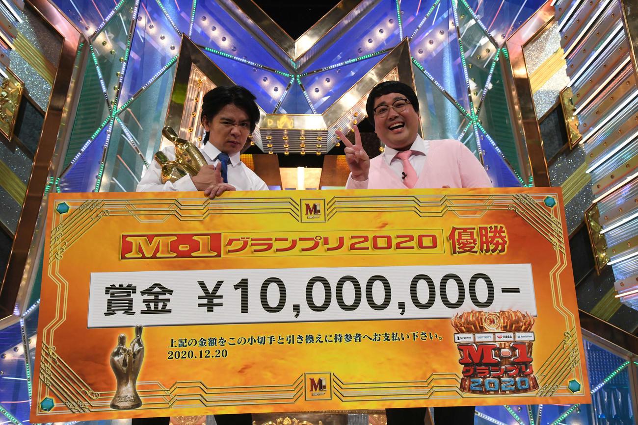 M-1グランプリ2020で優勝し、優勝賞金ボードとトロフィーを手にする「マヂカルラブリー」の野田クリスタル(左)と村上(C)M-1グランプリ事務局