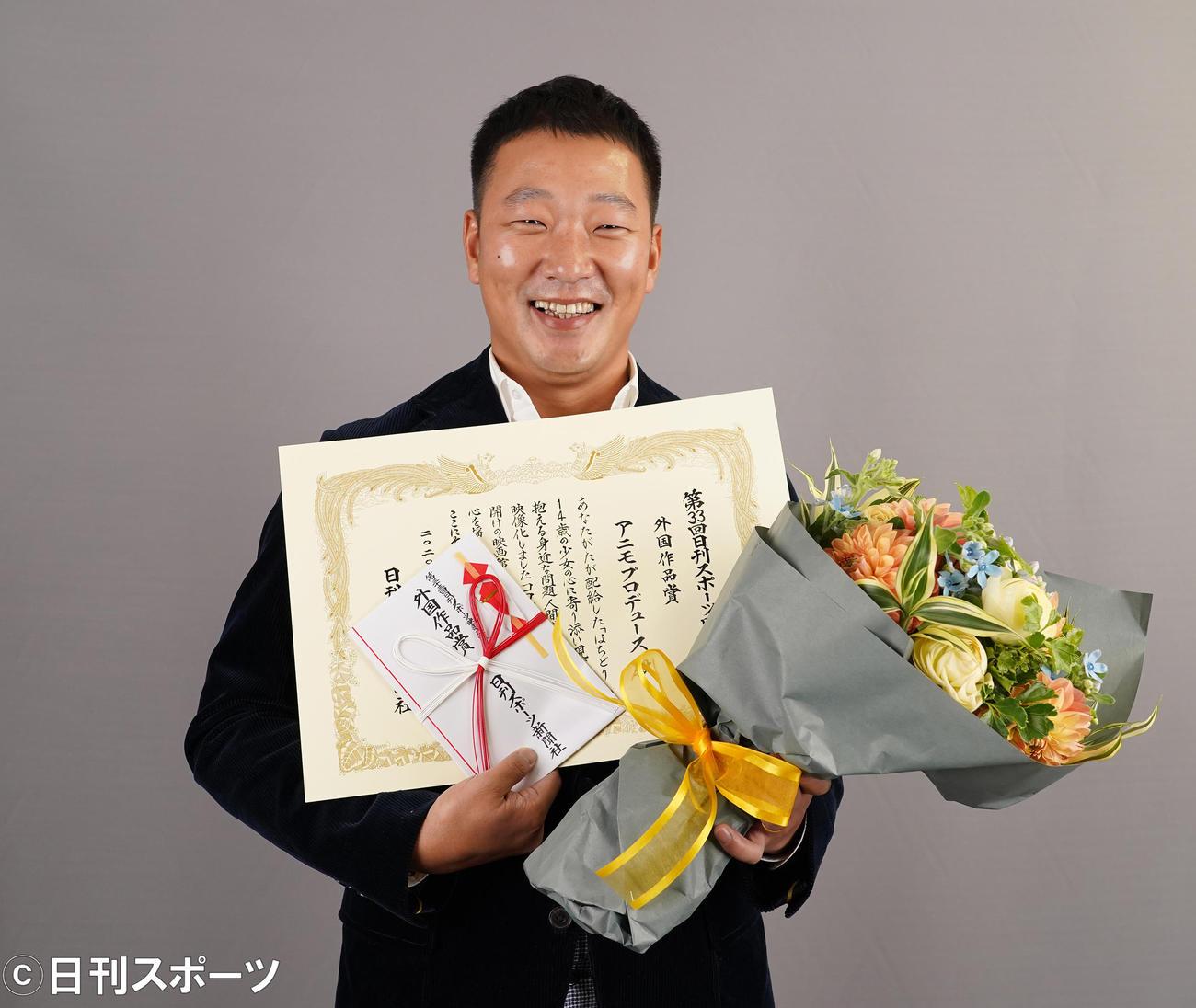 「はちどり」で外国作品賞を受賞し、表彰状と花束を手に笑顔を見せるアニモプロデュース成宏基代表(撮影・菅敏)