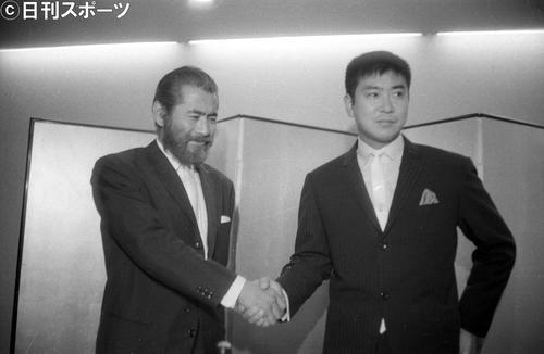 がっちり手を握り合って共同製作の実現を喜び合う三船敏郎さん(左)と石原裕次郎さん(1964年10月1日撮影)