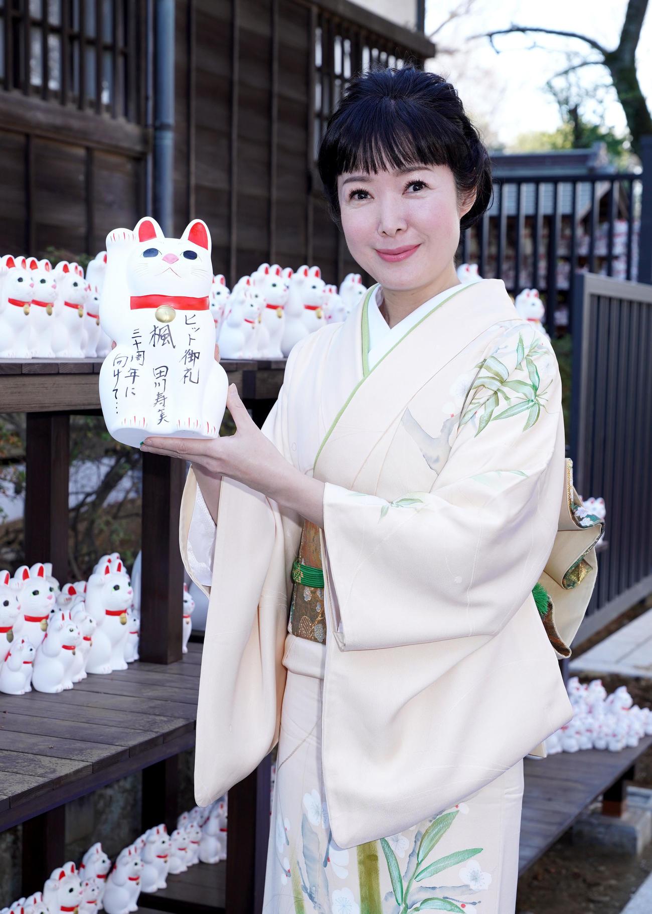ヒット御礼の招き猫を奉納する田川寿美(東京・豪徳寺)