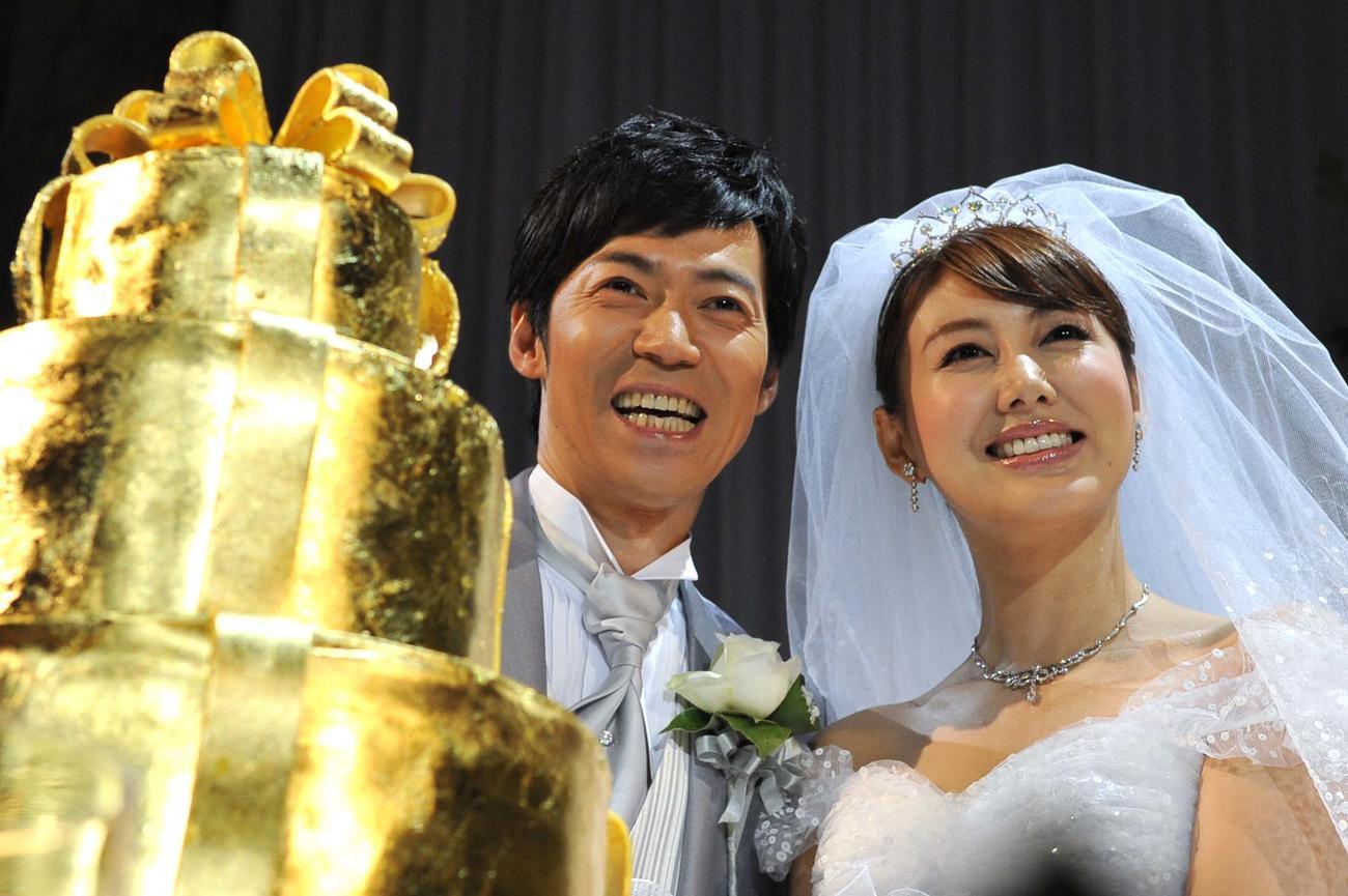 金のウエディングケーキを前に笑顔を見せる東貴博(左)と安めぐみ=2012年7月8日
