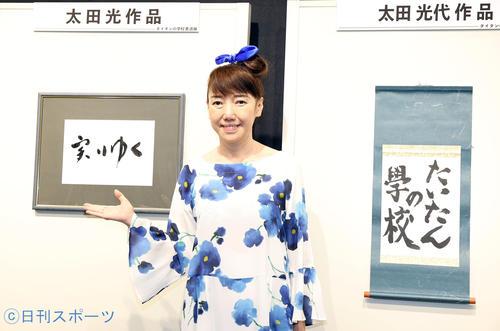 「タイタンの学校 書道展」で、自書「たいたんの学校」と太田光書の「実りゆく」の作品の前でポーズをとる太田光代(撮影・浅見桂子)