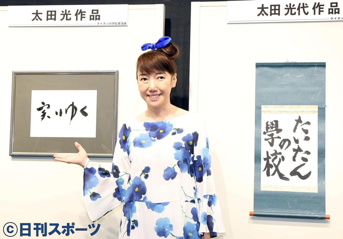 「タイタンの学校 書道展」で展示された作品を背にポーズをとる太田光代氏(撮影・浅見桂子)