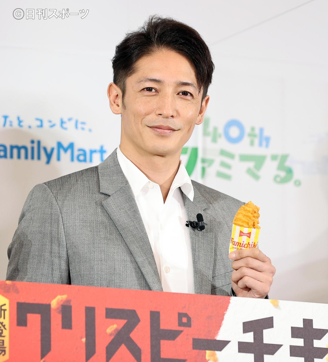 ファミリーマート創立40周年記念発表会で、新商品のクリスピーチキンを手に笑顔を見せる玉木宏(撮影・浅見桂子)
