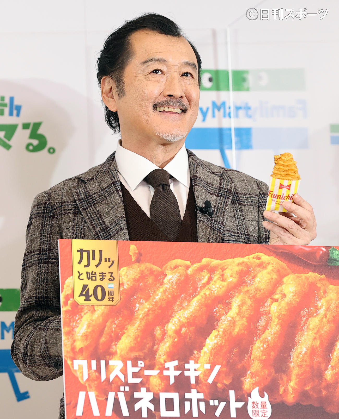 ファミリーマート創立40周年記念発表会で、新商品のクリスピーチキンを手に笑顔を見せる吉田鋼太郎(撮影・浅見桂子)