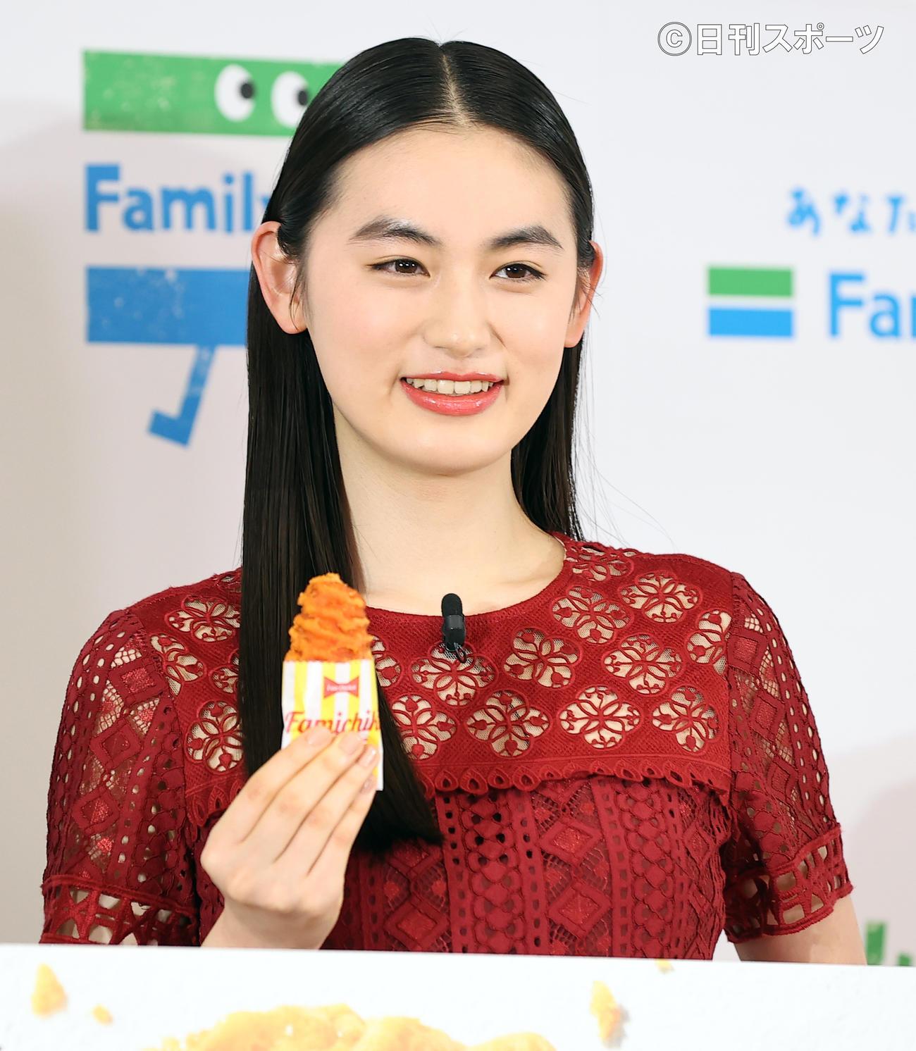 ファミリーマート創立40周年記念発表会で、新商品のクリスピーチキンを手に笑顔を見せる八木莉可子(撮影・浅見桂子)