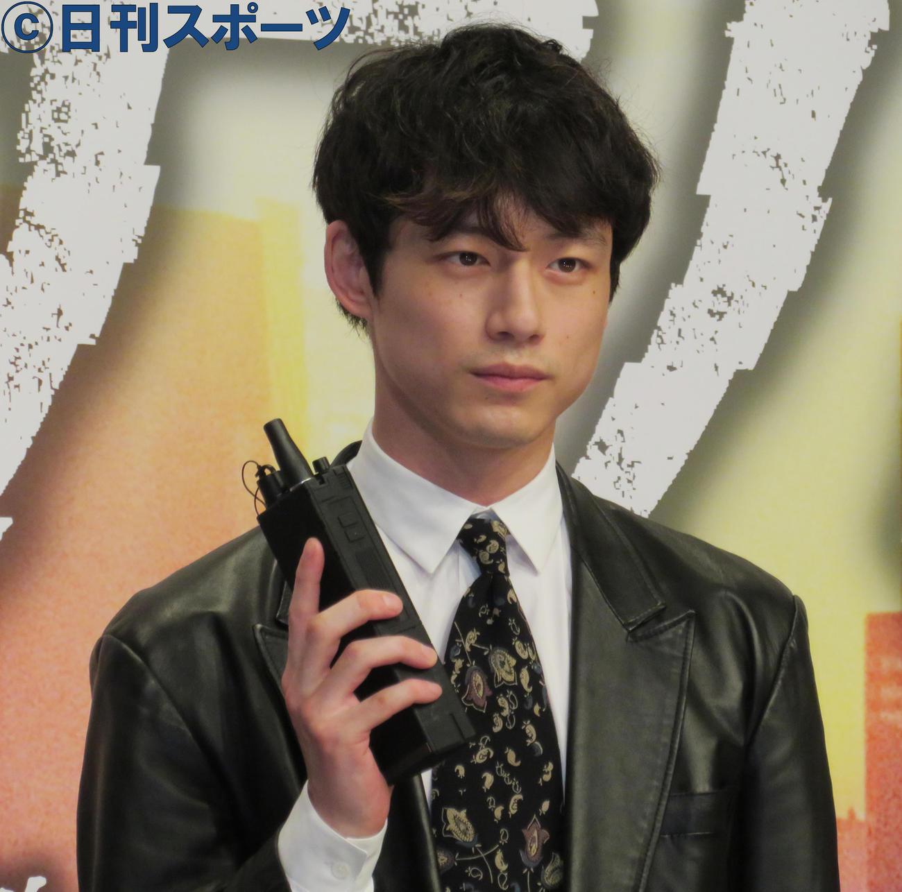 完成報告会に出席した坂口健太郎はトランシーバーを手にポーズをとる(撮影・佐藤勝亮)