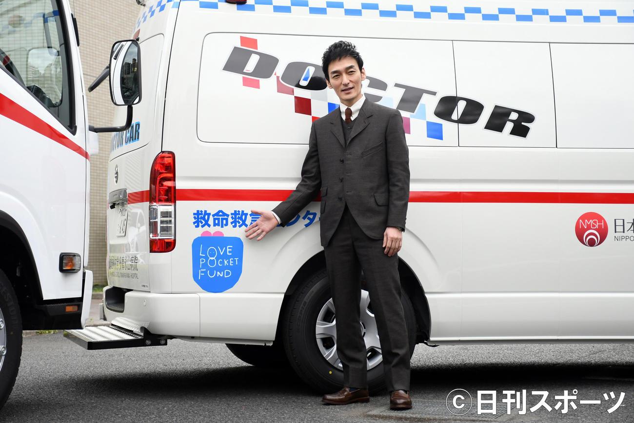 ドクターカーについている「LOVE POCKET FUND」のマークを指す草なぎ剛(撮影・大友陽平)