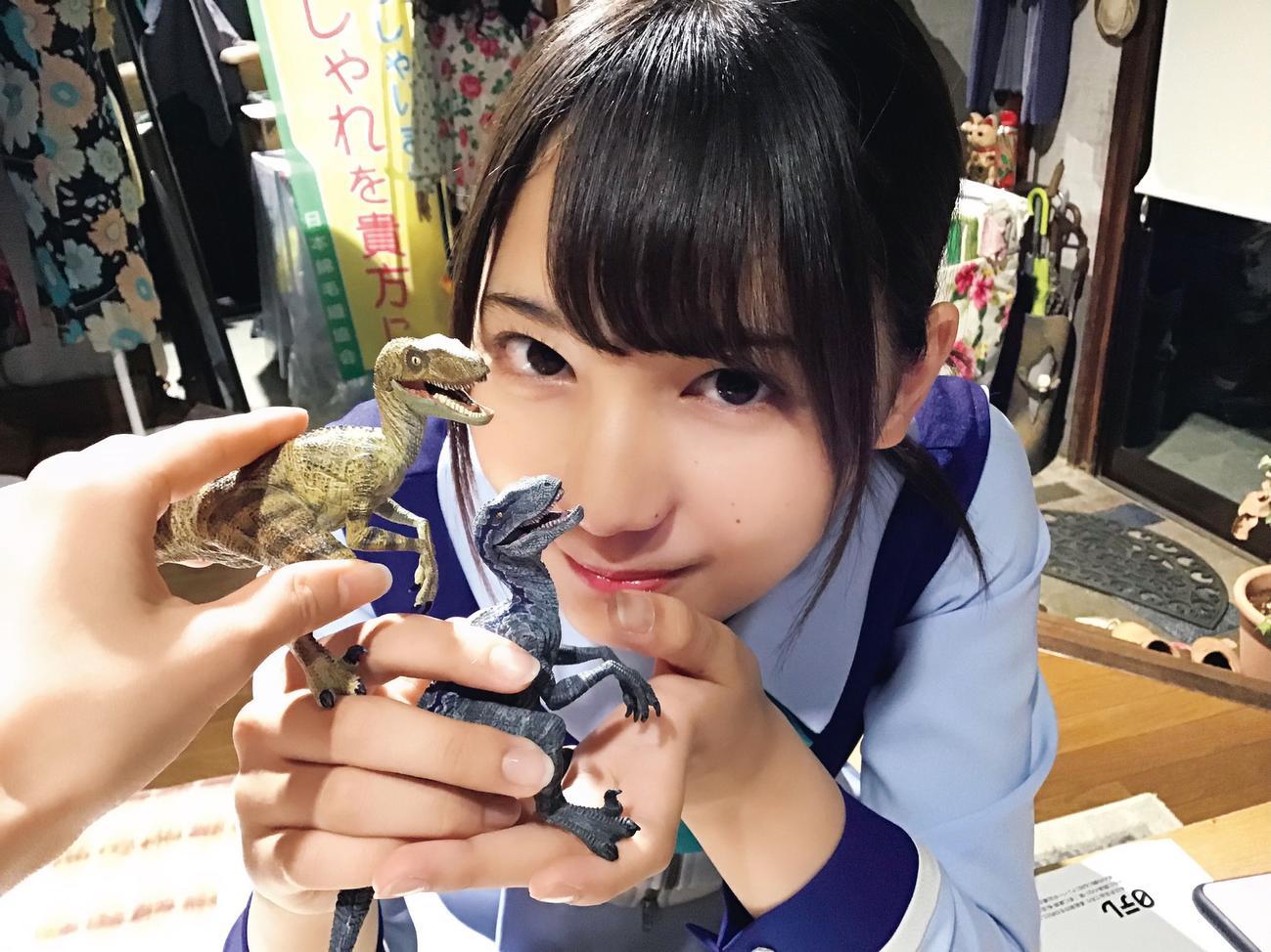 「日向撮」先行カット。恐竜のフィギュアを持って笑顔を見せる小坂菜緒。齊藤京子が撮影した