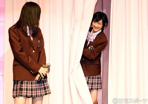 12年1月、新CM発表会で乃木坂46の高山一実(左)をカーテンを開けてのぞく生駒里奈