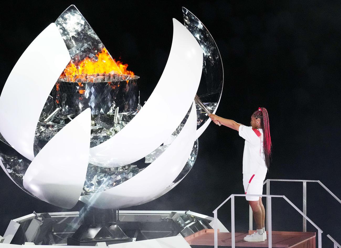 23日開会式で、最終聖火ランナーの大坂なおみは聖火台にトーチをかざす