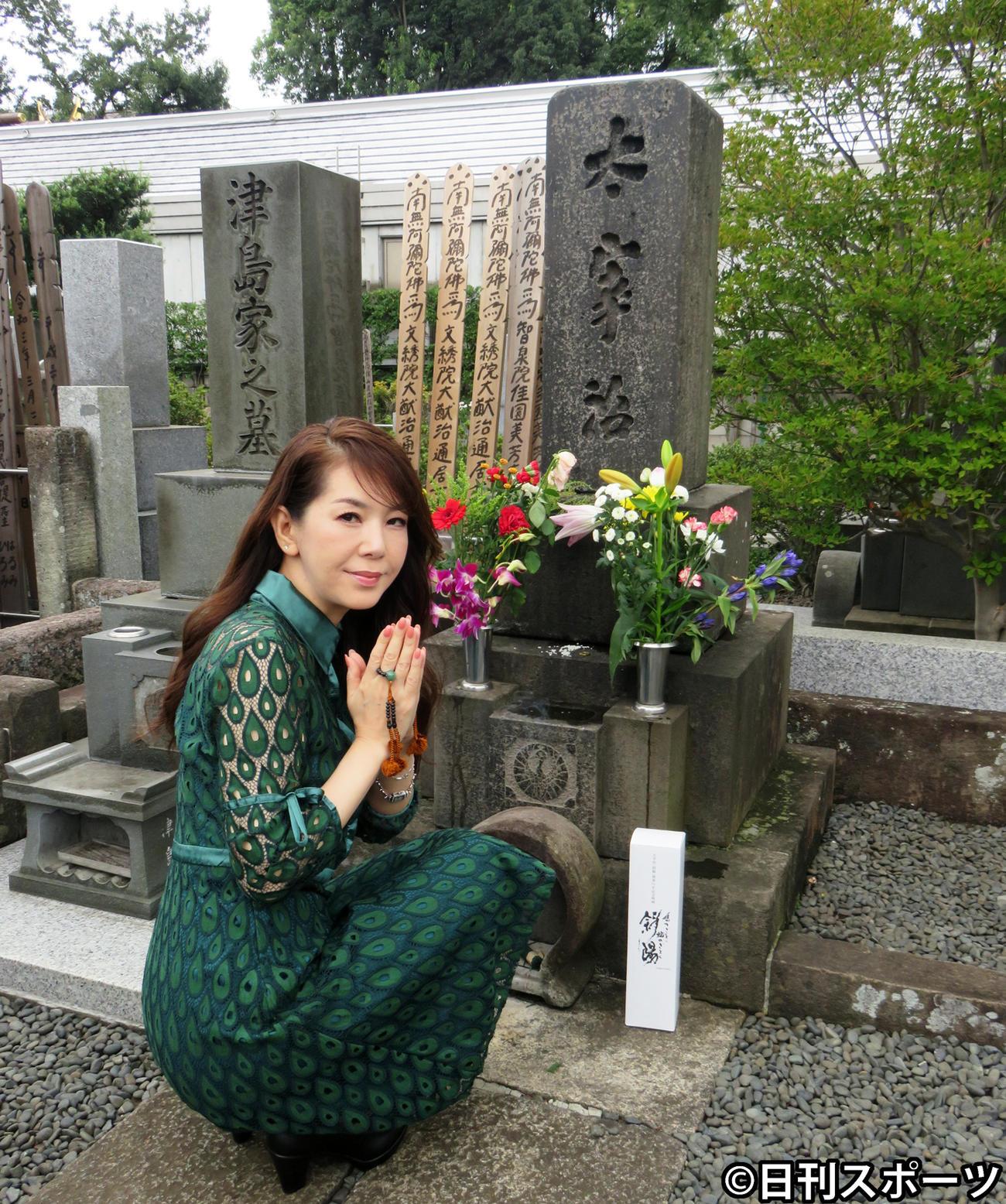 太宰治の墓の前で手を合わせる白石恭子(撮影・小谷野俊哉)