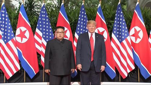 米朝首脳会談で初対面し記念撮影するトランプ米大統領と北朝鮮の金正恩委員長(AP)