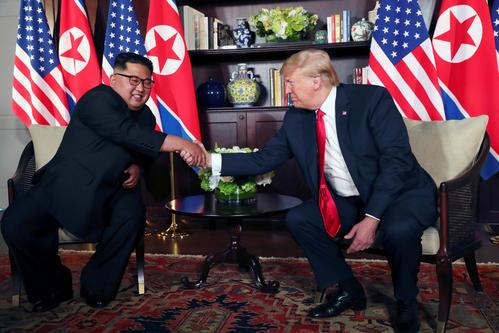米朝首脳会談前に握手するトランプ米大統領と北朝鮮の金正恩委員長(ロイター)