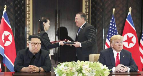合意文書の署名式に臨んだ北朝鮮の金正恩朝鮮労働党委員長(手前左)とトランプ米大統領。後方は文書を交換する金与正党第1副部長(左から2人目)とポンペオ米国務長官(ロイター=共同)