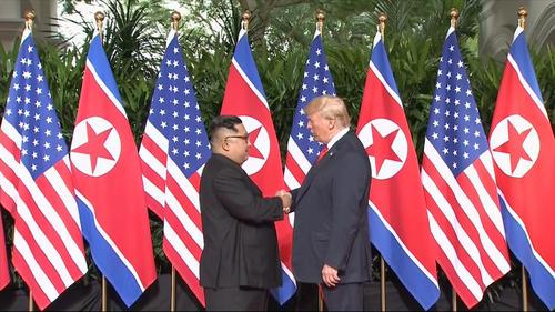 米朝首脳会談で初対面し握手するトランプ米大統領と北朝鮮の金正恩委員長(AP)