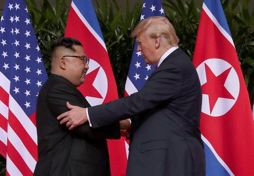 米朝首脳会談で初対面し握手するトランプ米大統領と北朝鮮の金正恩委員長(ロイター)