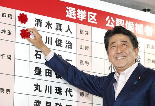 自民党本部の開票センターで、当確者の名前にバラを付ける安倍首相(共同)