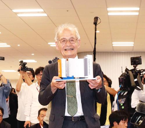 リチウムイオンバッテリーの模型を手に笑顔で写真に納まる「ノーベル化学賞」受賞の旭化成名誉フォローの吉野彰氏(撮影・河田真司)