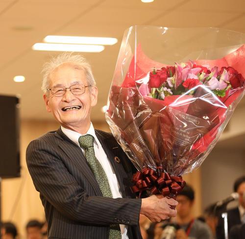 会見場で祝福される中、花束を抱え満面の笑顔を見せるノーベル化学賞受賞を決めた旭化成名誉フェローの吉野彰氏(撮影・河田真司)
