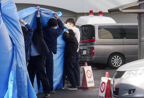青森県八戸市で女子児童が切り付けられた事件で、送検のため青森県警八戸署を出る男子生徒を乗せた車(右)(共同)