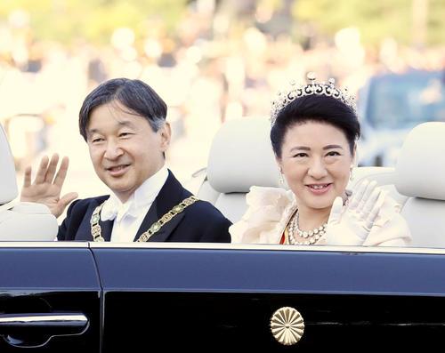 即位を祝うパレードで沿道の人々に手を振られる天皇、皇后両陛下(2019年11月10日撮影)