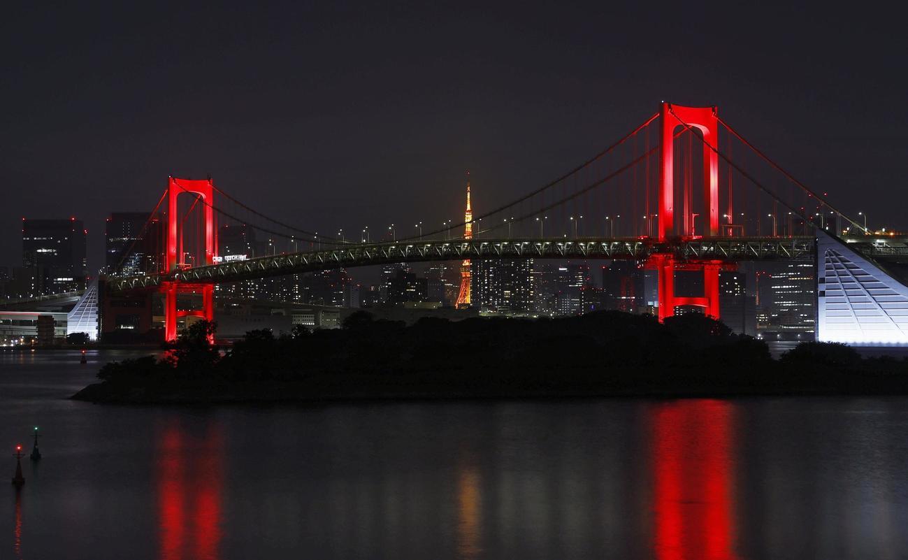 初の「東京アラート」が発令され、赤く点灯された東京湾に架かるレインボーブリッジ。後方中央は東京タワー=2日深夜(共同)