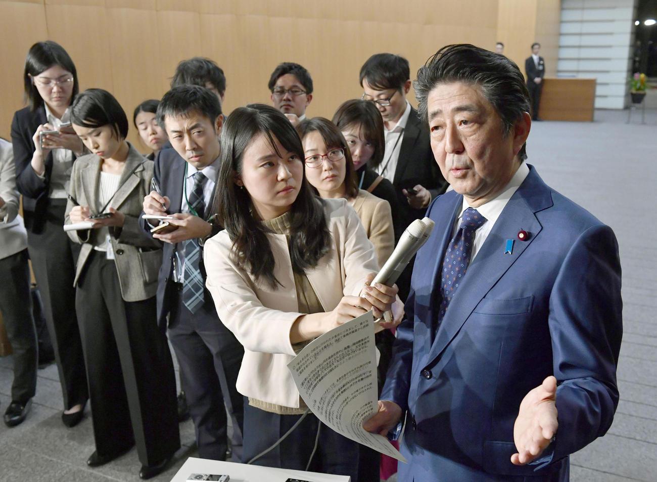 19年11月、「桜を見る会」を巡り、記者団の質問に答える安倍首相(当時)(共同)