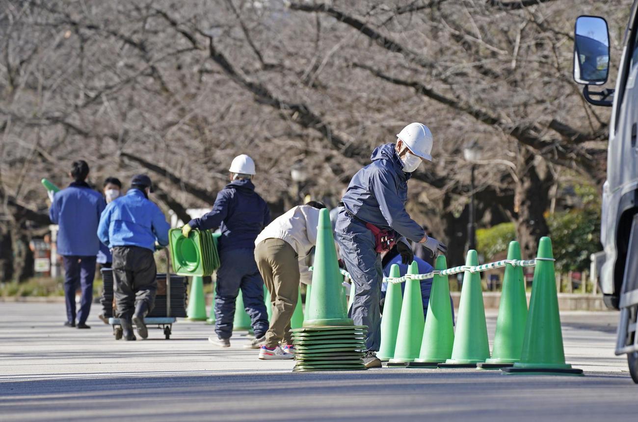 新型コロナウイルス感染拡大防止のため、東京・上野公園の大通りにパイロンを設置し片側通行にする作業員ら(共同)