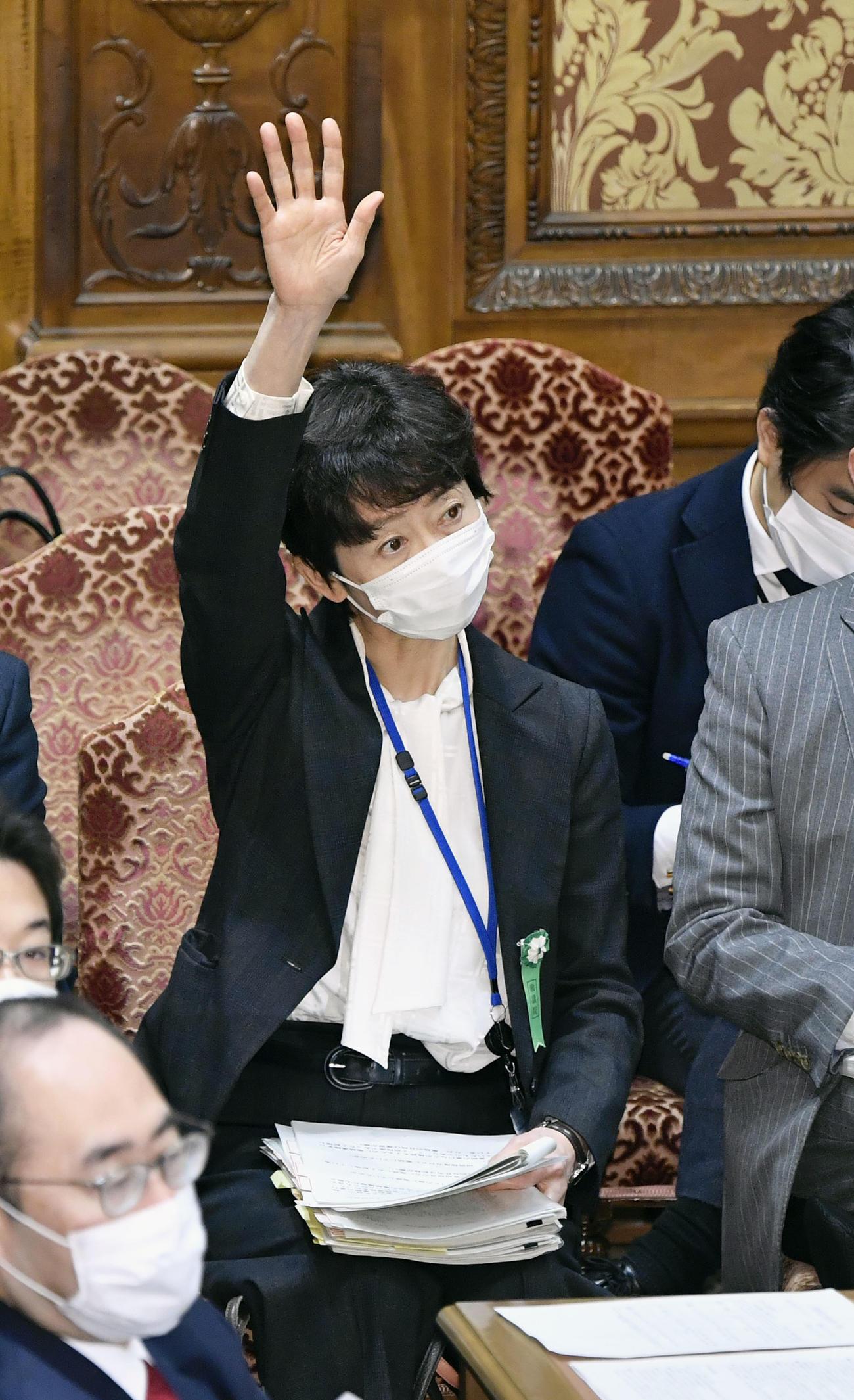 衆院予算委で答弁のために挙手する山田真貴子内閣広報官(共同)