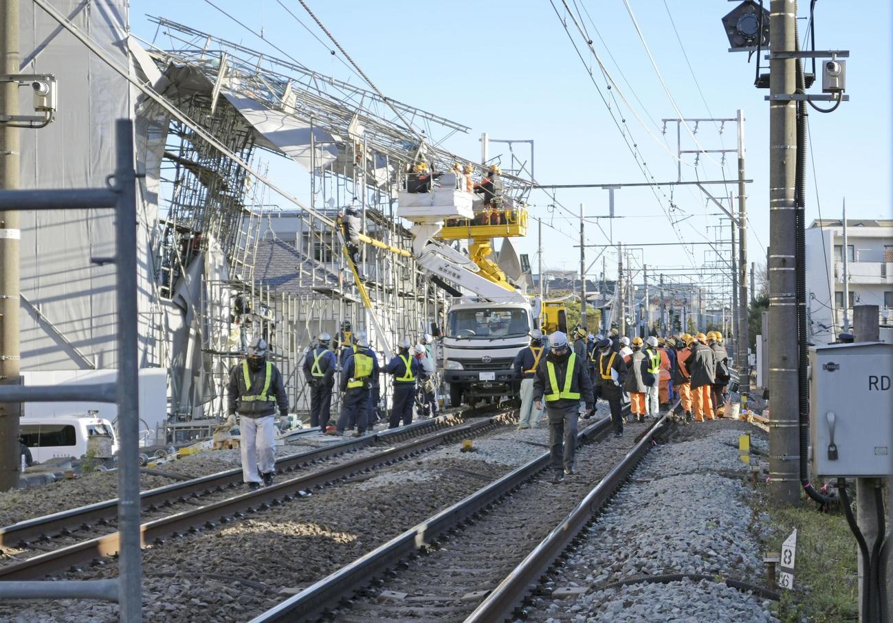 東急東横線の線路脇で起きたビル建設現場の足場崩落事故で、復旧作業にあたる作業員ら(共同)