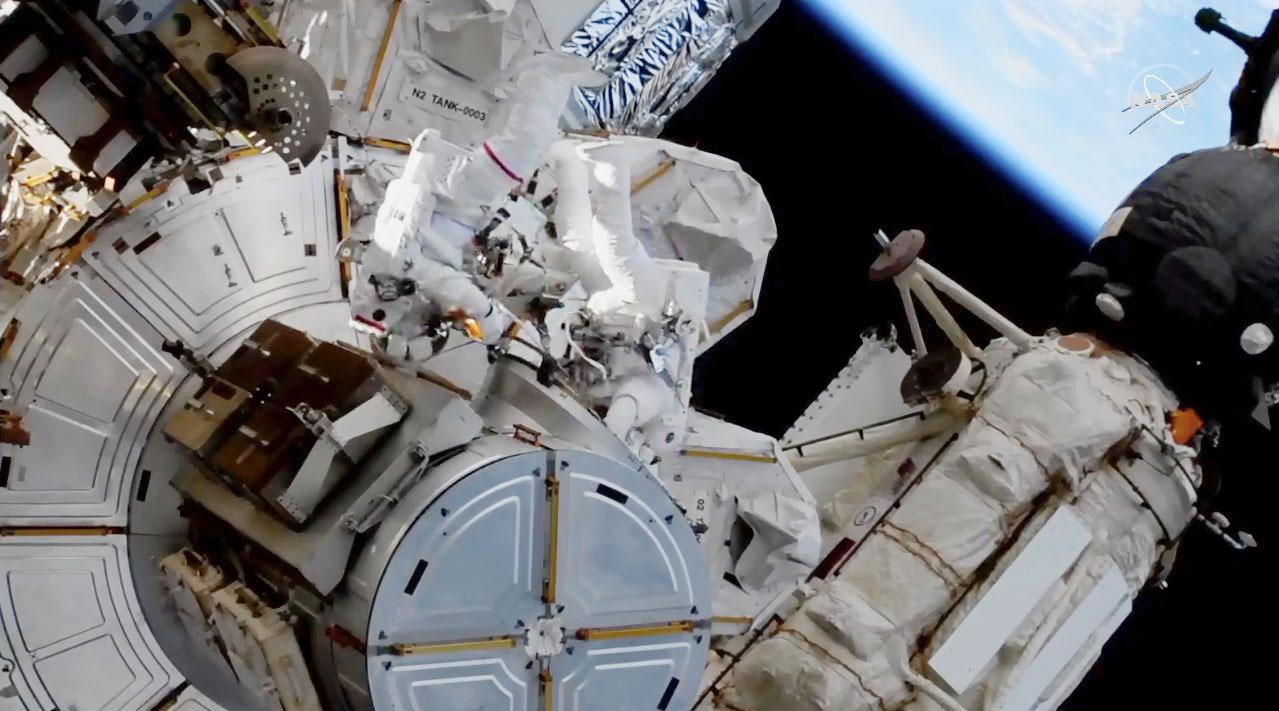 4回目の船外活動のため国際宇宙ステーションを出る野口聡一飛行士(右)ら(NASAテレビから)