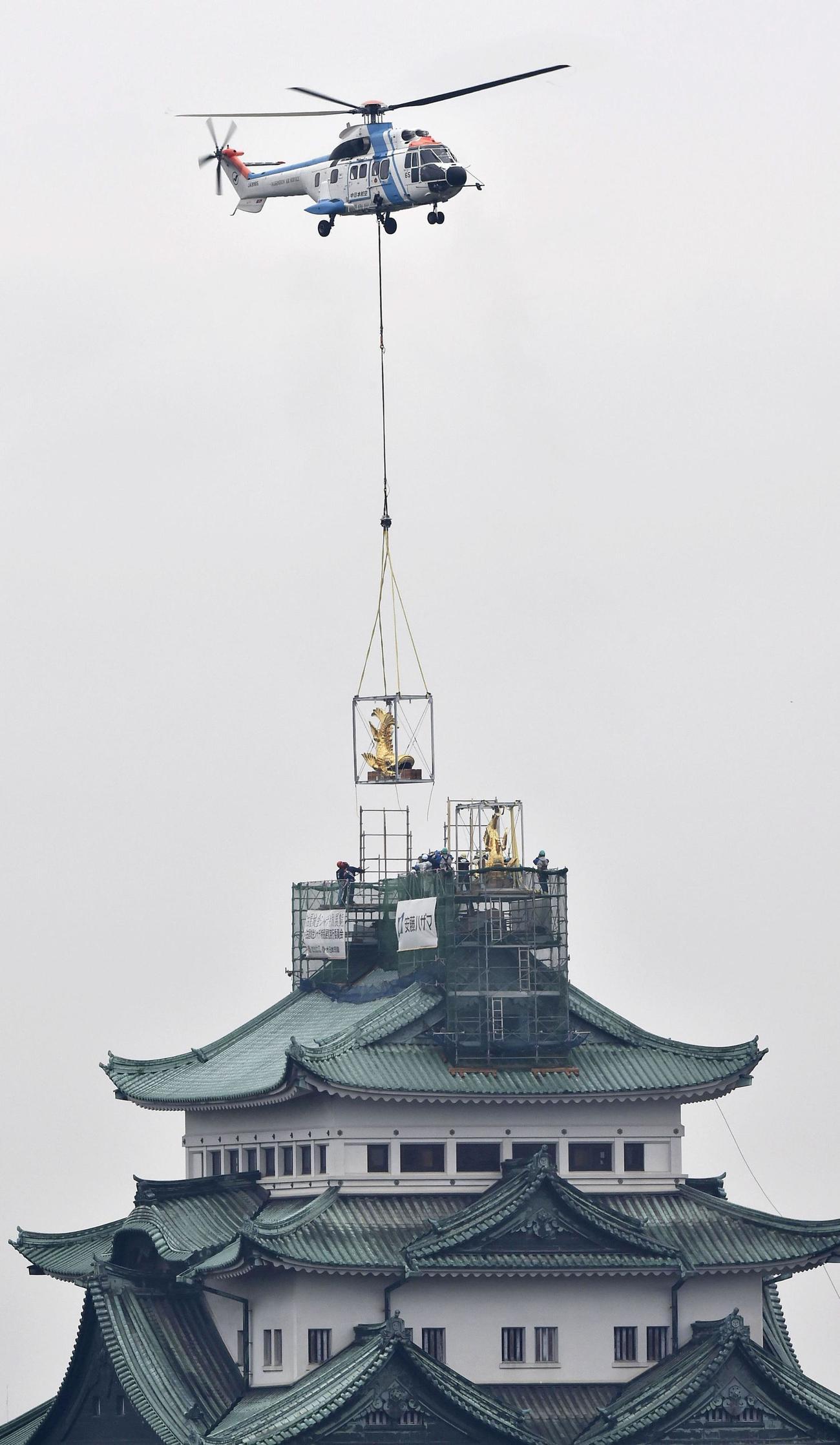 ヘリを使って名古屋城天守から取り外される「金のしゃちほこ」(共同)