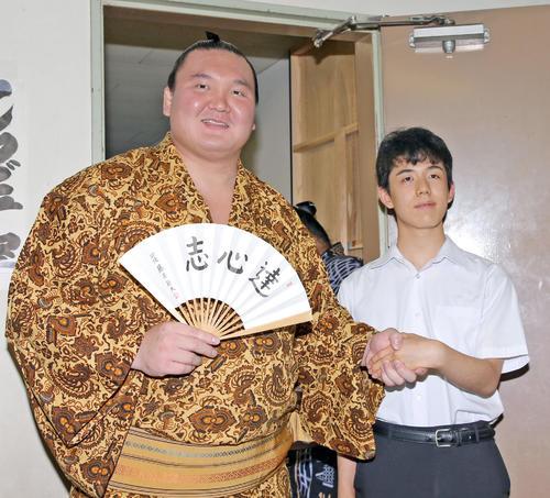 藤井四段(右)は支度部屋を訪れ、直筆の扇子をプレゼントした白鵬と握手(撮影・加藤哉)