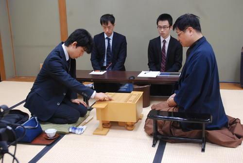 初手を指す藤井聡太四段(左)と小林健二九段(撮影・松浦隆司)