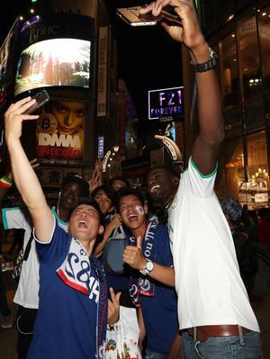 渋谷のスクランブル交差点でセネガルサポーターと記念撮影する日本サポーター(撮影・狩俣裕三)