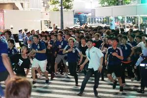 日本の1次リーグ突破が決まり渋谷のスクランブル交差点を駆け出すサポーター(撮影・足立雅史)