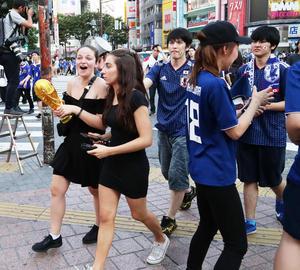 W杯トロフィーのレプリカを手に盛り上がる外国人の後方で悔しそうな表情を見せる日本人サポーター(撮影・足立雅史)