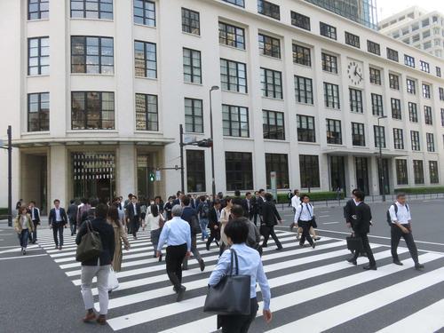 10日、10連休明けに東京・丸の内のオフィス街を行き交う会社員ら
